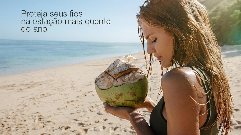 Mulher na praia bebendo água de coco