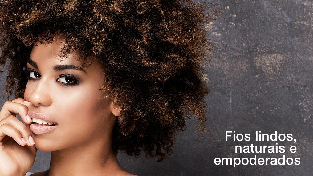 Mulher com cabelo natural cacheado, escrito a frase na imagem: Fios lindos, naturais e empoderados